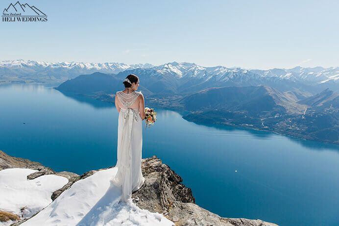 bride shows off the back of her gown on spring day. Destination Heli weddings Queenstown.