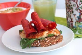 Maukas, jyväinen Kultakaura-leipäviipale tarjoillaan aamiaisella halloumijuuston ja salamimakkaran kera.