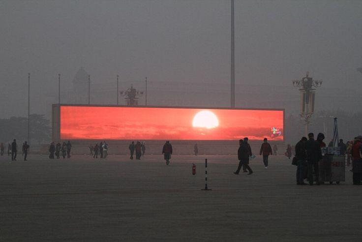 Una fitta nebbia grigia, su cui splende un tramonto proiettato su un maxi schermo. E' una delle conseguenze dell'emergenza inquinamento atmosferico in Cina, dove le polveri sottili hanno raggiunto nuovi record di concentrazione. A Pechino - una delle città maggiormente interessate - la visibi