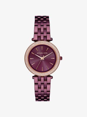 A little glam, a little girl next door—our mini Darci watch delivers chic attitude every time. A pavé-embellished bezel and rose gold-tone accents shine against the rich plum-hued hardware. Wear it solo or pair it with a sleek bangle for an elegant mix.