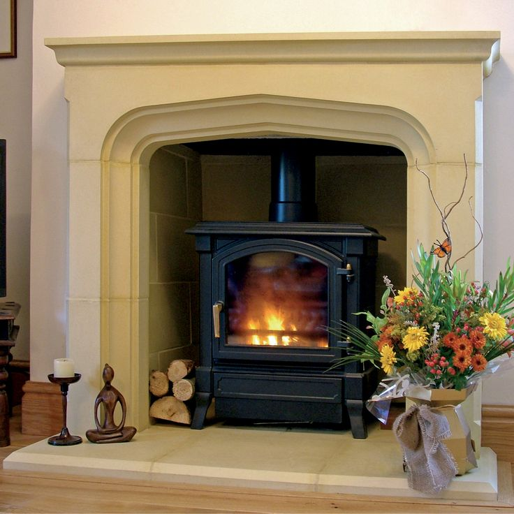 The Tall Manor Fireplace from Haddonstone shown with a wood burning stove