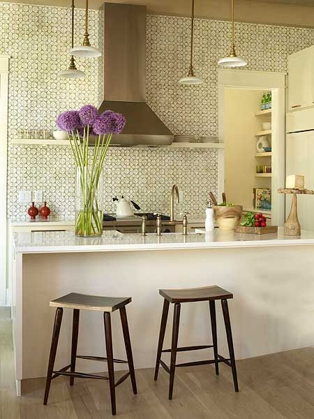 In this cozy kitchen, tiles give the illusion of wallpaper, but they are much easier to clean. Keep an open kitchen from looking too hardworking by concealing appliances like refrigerators behind cabinetry. (Photo: Tria Giovan)