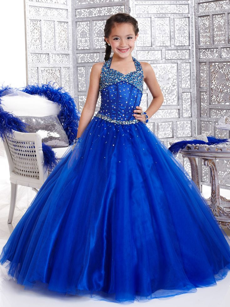 Dazzling Tiffany Glitz Children Pageant Dress 33424. This tulle pageant dress displays a halter neckline, heavily beaded straps and bust, fitted corset bodice, and a ball gown skirt with scattered beading. Beautiful and affordable dress perfect for your special occasion. Available in Royal, Party Pink and Tangerine.