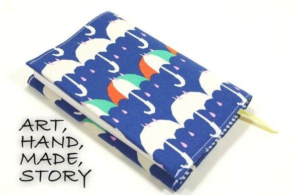 青地に傘柄がキュートな文庫サイズのブックカバーです。内側は青のストライプでさわやか風です。ピッタリなサイズ感で使い心地が良いと思います。片方が差し込み式で本の...|ハンドメイド、手作り、手仕事品の通販・販売・購入ならCreema。