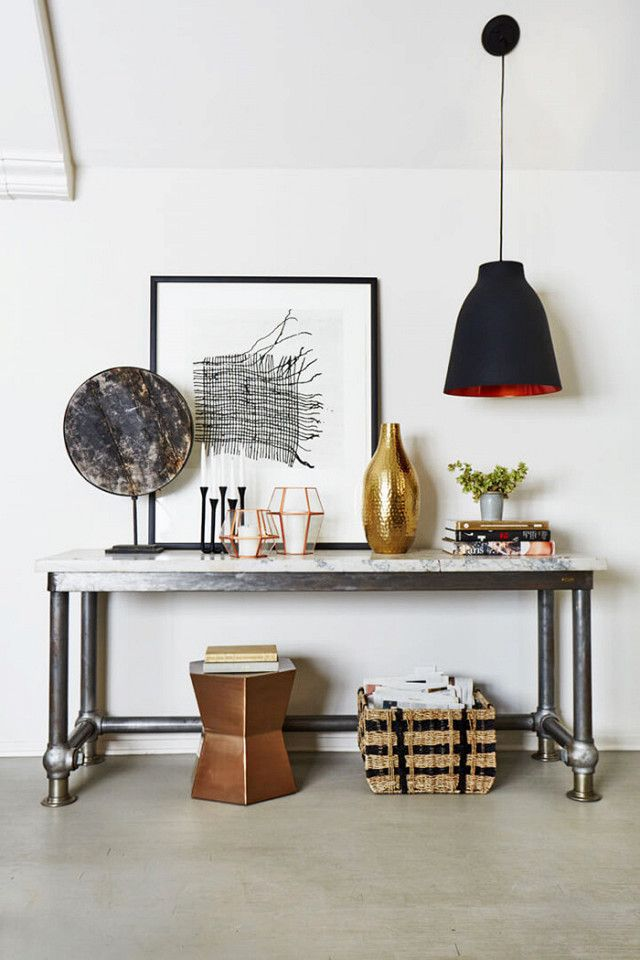 Entryway vignette with a marble and steel table, art, sculptures, and a low-hanging black pendant light