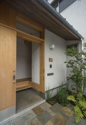 造作の玄関引戸。汚れと腐れ防止のため、下の部分にステンレス板金を施してある。軒裏は杉板に自然塗料。