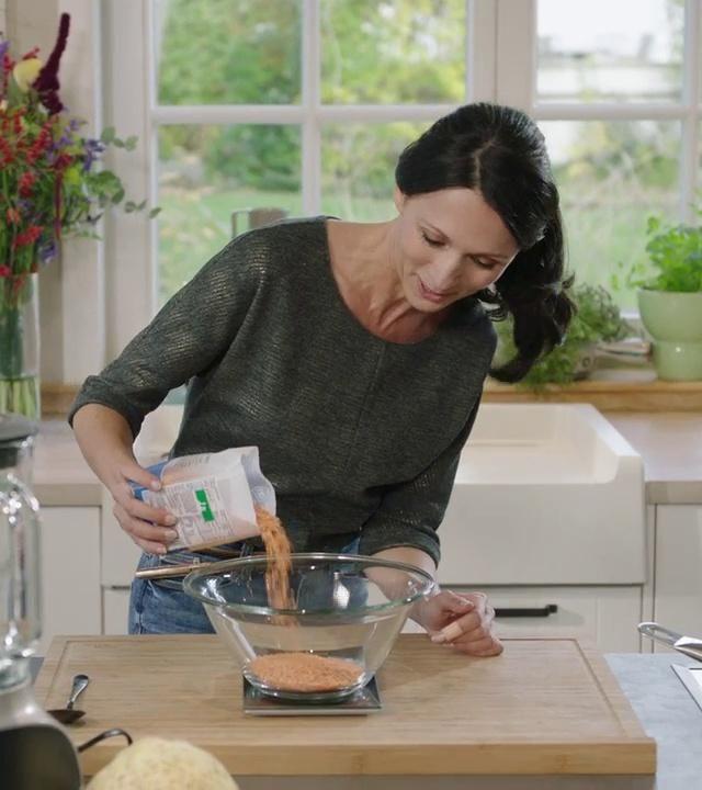 Sandra weegt 125 gram rode linzen met een keukenweegschaal van Cosy & Trendy