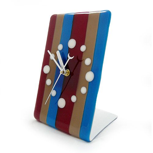 "Modern Fused Glass Desk Clock: Candy Stripe. Conventional clock numerals are replaced with simple white circles, contrasting against the robust shades of blue, maroon, and mocha in bold vertical stripes. The lively design is permanently fused by means of kiln-firing the glass at extreme temperatures. With the addition of clock hands, the fused glass becomes an admirable work of functional art for your contemporary space! Measures approximately 8"" tall. Requires 1 'AA' battery."