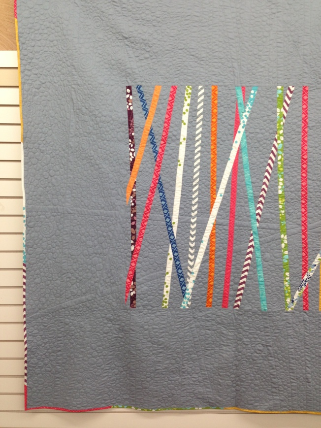 Cross it. Gray background quilt with pick-up stick type strips in the center.