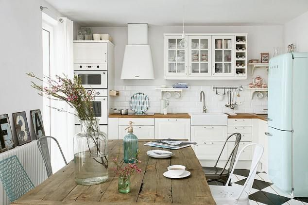 White shaker-style kitchen, with white splash-back tiles and oak worktops