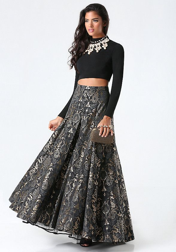 Sumptuous 2-piece gown pairing a sleek jersey crop top with a metallic jacquard skirt. Extended front pleats and a ruffle-trimmed tulle underlayer add sweeping volume. Top has back hook-and-eye and exposed zip closure. Skirt has hidden back hook-and-eye and zip closure. Skirt is fully lined.