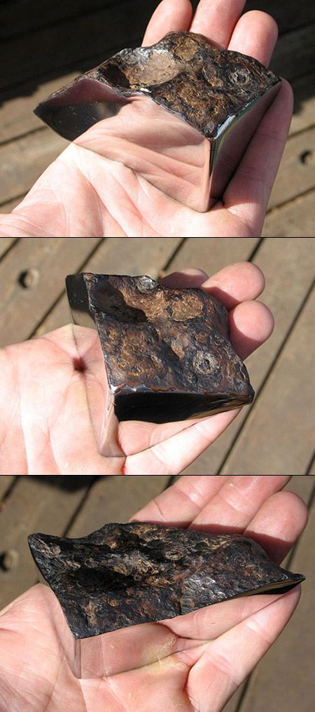 Seen here is a 773 gram polished Chinga meteorite. The quarter-cut specimen was found in Turvinskaya, Russia and has been cut and polished on two sides. The rest of the meteorite retains its natural light brown crust, creating a dramatic contrast.