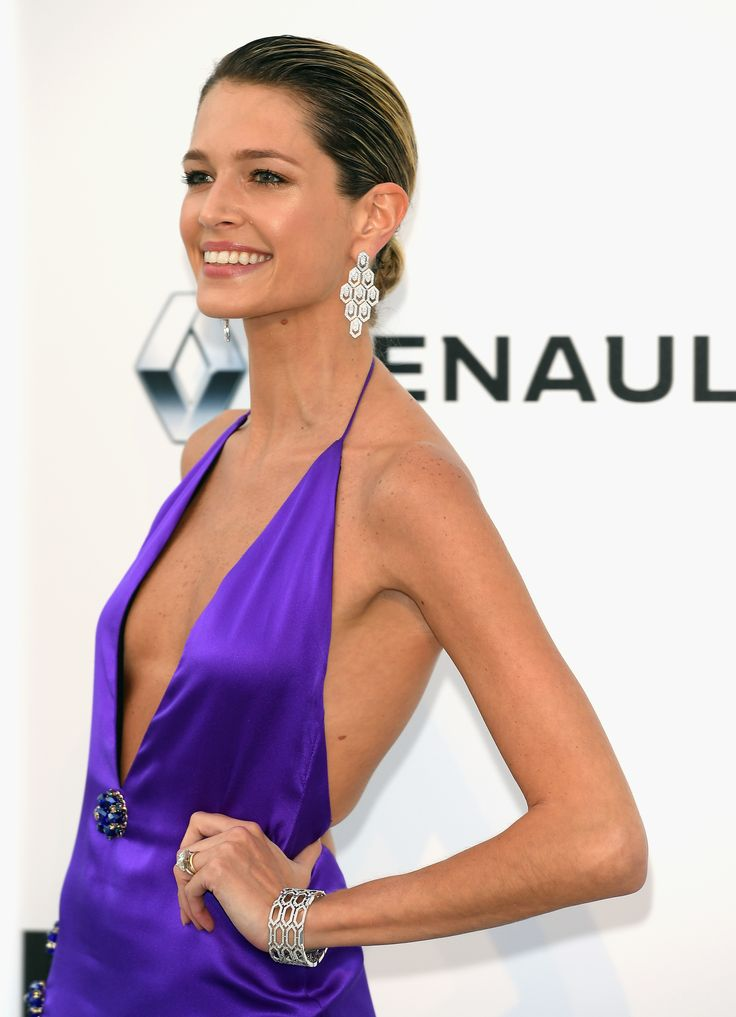 Brazilian blogger Helena Bordon wore diamond Bulgari Serpenti earrings in white gold and a Serpenti bracelet with diamonds and emerald with her bright violet purple low cut V-neck satin dress. Slick back hair do. At the amFAR Gala. For glamour celebrity fashion Cannes Film Festival red carpet jewellery spotting travel here: http://www.thejewelleryeditor.com/jewellery/top-5/cannes-film-festival-amfar-gala-2017-red-carpet-jewellery/ #jewelry