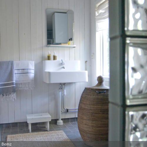 Die weiße Holzverkleidung im Badezimmer sorgt für skandinavische Natürlichkeit. Mit einem Sisalteppich und einem Wäschekorb aus Bast wird der natürliche Effekt…