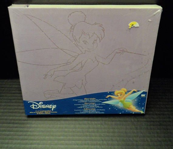 $19.89 + calculated (global) shipping~   NEW in package purple 8 x 8 scrapbook album/Memory Keepsake featuring Disneys Tinkerbell character.  Tinkerbell is outlined in glitter on the albums cover.  Album is by EK Success. ~Includes 10 side loading page protectors, 10 spine spacers.... ...2 post extenders and 1 extended spine cover.  Post-bound album.
