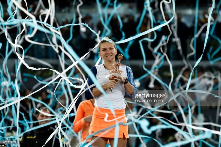 Romanian tennis player Simona Halep poses with her trophy as she celebrates her victory over French tennis player Kristina Mladenovic after the WTA Madrid Open final in Madrid, on May 13, 2017. Halep won 7-5, 6-7 and 6-2. /