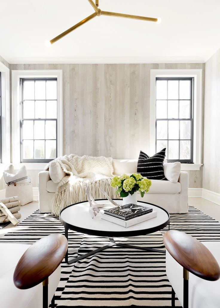 rustic inspired living room with light white washed wood grain wallpaper, white floors, creams sofa, black and white accents
