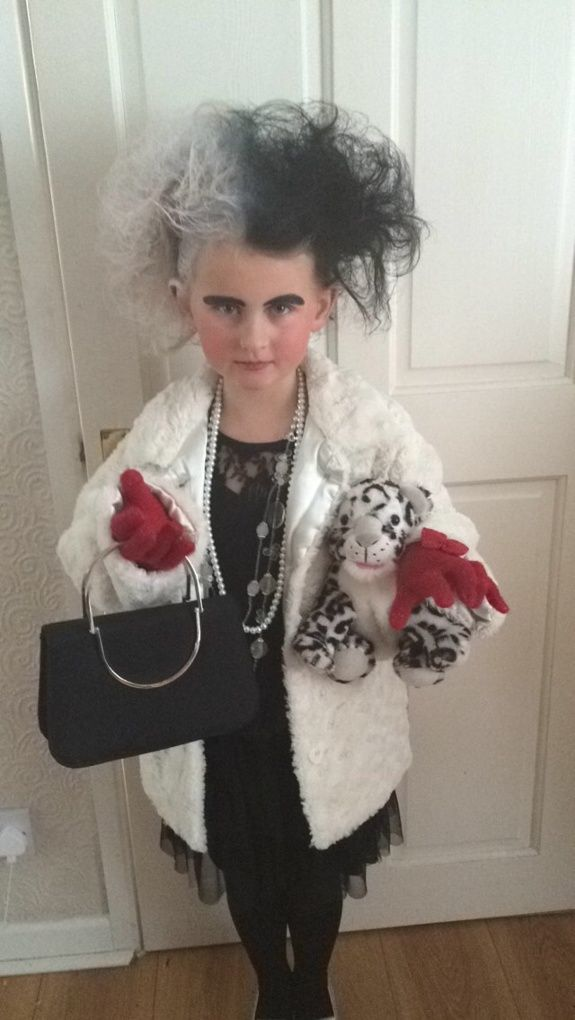 dressed as Cruella De Vil from 101 Dalmatians. Black dress and tights, old white beads, black handbag. Spotty dog (snow leopard). Eyeliner for eyebrows, old winter fur coat. Lots of back combing and hair spray finished with hair spray colours