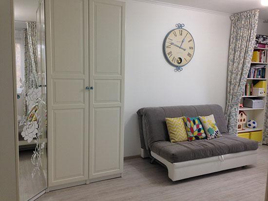 Серый диван в гостиной, большие круглые часы на стене, белый шкаф фото