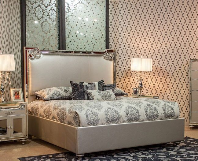 the ornate champagne upholstered bed with mirror trim on the edges of mirror