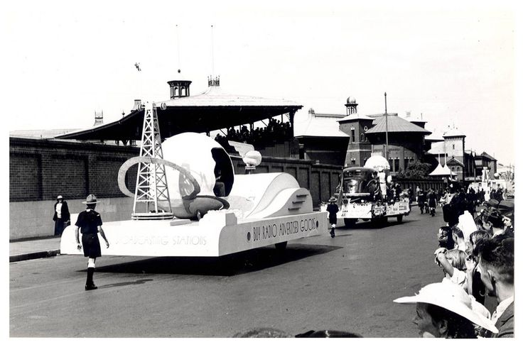 """Image 21806141 - The 'Radio Broadcasting Stations' float, which formed part of the """"Australia's March to Nationhood"""" parade on January 26th, 1938. This image was taken in Driver Avenue, Moore Park. The float is adorned with the slogan """"Buy Radio Advertised Goods"""". [RAHS Australia Day 1938 - Sesquicentenary Celebrations Collection]"""
