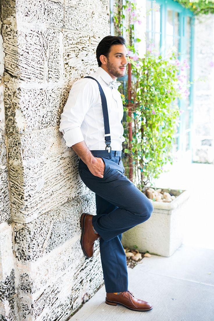 Handsome groom with suspenders in navy