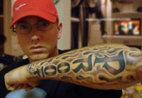 The back of the hand is decorated with tattoo Proof inscription. It is dedicated to his friend, with whom they were in the D12 group. In 2006, Proof was tragically killed by a bullet. This inscription was the last tattoo Eminem.