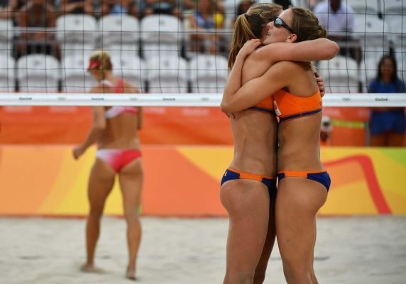 Sophie van Gestel and Jantine van der Vlist of the Netherlands celebrate after winning a point during the women's beach volleyball qualifying match between Canada and the Netherlands at the Beach Volley Arena in Rio de Janeiro on August 7, 2016, for the Rio 2016 Olympic Games.