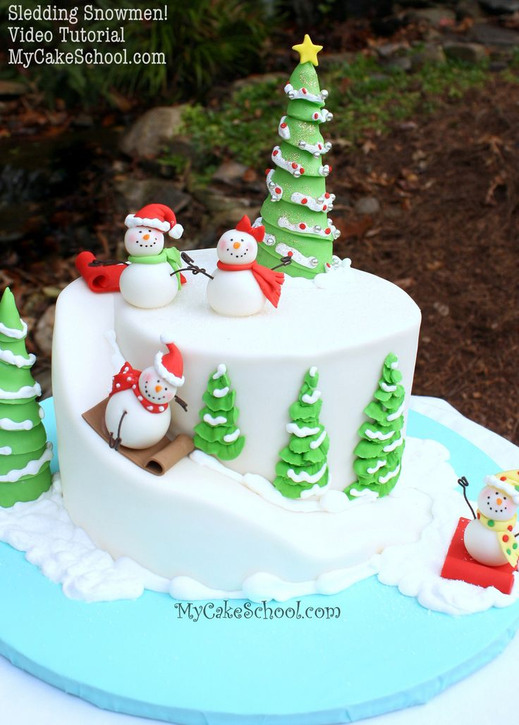 Learn to make an adorable winter-themed snowman cake with carved cake slope in this Sledding Snowmen Cake Tutorial by My Cake School!