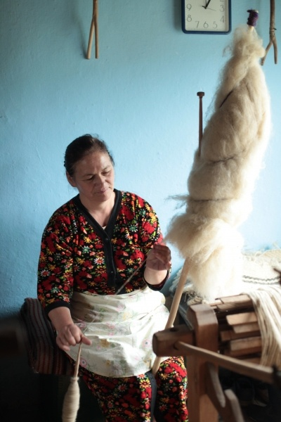 spinning wool from a well dressed distaff on a spindle, next to a loom