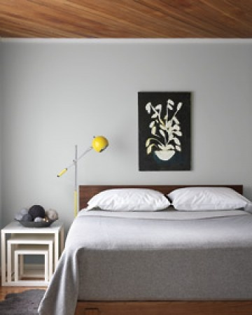 sleek bedroom. grey walls and yellow accent
