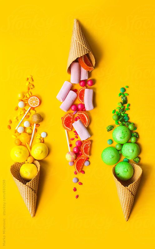 Different kind of colorful candies in ice cream cone on yellow background by Marko Milanovic, Food photography, food styling