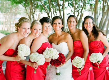 Red bridesmaids with hydrangea bouquets and bride with red rose bouquet | Photo: Justin DeMutiis Photography
