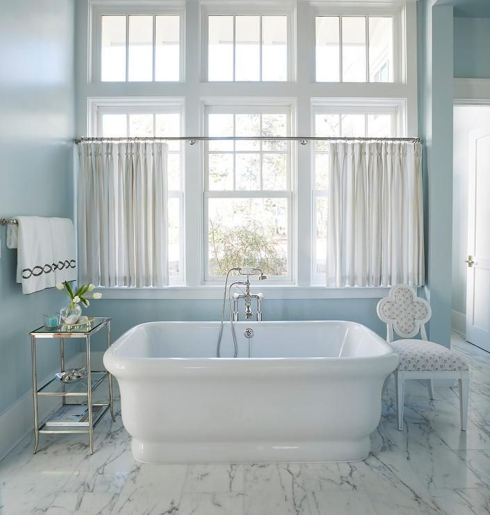 Blue cottage bathroom boasts windows dressed in light gray sheer cafe curtains hung above a freestanding rectangular bathtub fitted with a vintage style polished nickel tub filler.