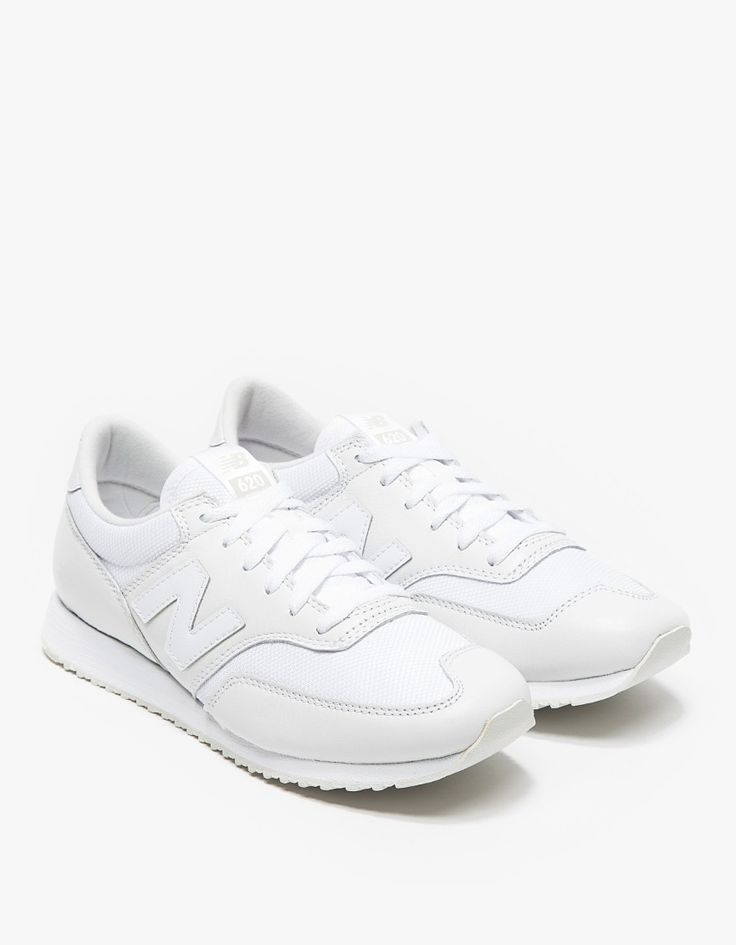 A classic vintage inspired 620 women's tennis shoe from New Balance in all white. Features premium leather uppers, padded collar, tongue, stitched logo ankle cap, and lug soles. • Retro running shoe in all white • Leather uppers • Padded collar • S