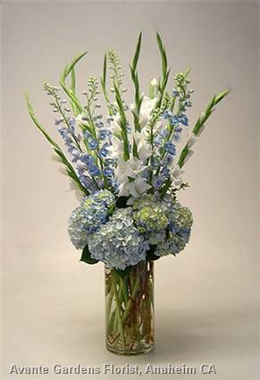 A large-scale casual contemporary arrangement featuring pale blue hydrangeas, light blue hybrid delphiniums and white gladiolas in a cylinder vase.