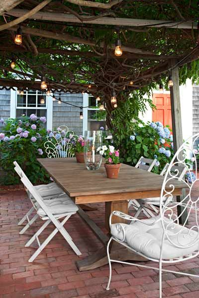 A wisteria-draped pergola is a favorite gathering spot for meals all summer long.   Photo: Eric Roth   thisoldhouse.com