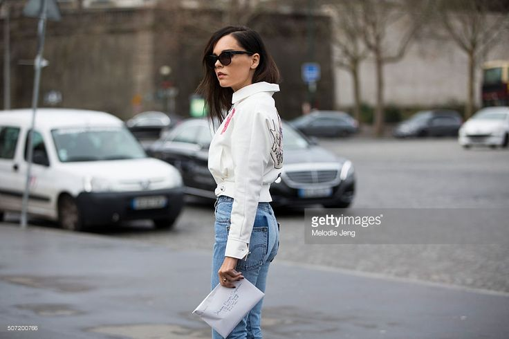 Evangelie Smyrniotaki wears an Olympia Le Tan ropped white zipped jacket with prints and 'Down the Rabbit Hole' princess print and Vetements jeans at the Elie Saab Couture show at Trocadero on January 27, 2016 in Paris, France.