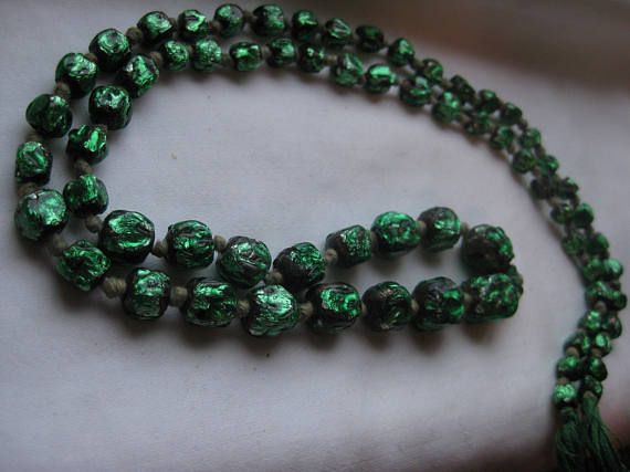 I have researched, trying to discover the use of this strand of beautiful green and black Foil Beads. I have found nothing. It was either made as an example, or had a purpose such as a tie back or accessory attachment Im thinking if it were wrapped twice around the wrist and tied? or perhaps a choker? Maybe you would take them apart to use in other projects. Or just display them in boudoir, as I have all these years. brilliant color, 65 beads in all, graduating in size to one larger one at…