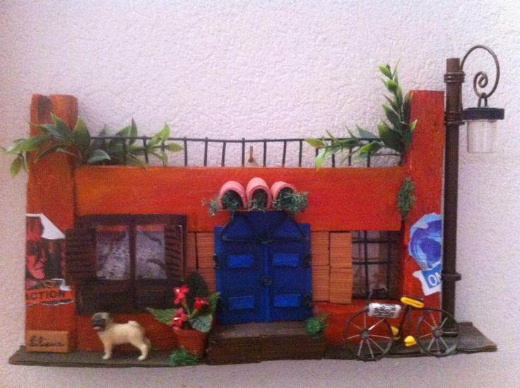 Un cagnolino e una bicicletta animano la facciata di questa casetta dal portone blu.