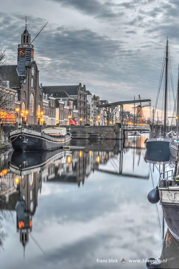 De avond valt boven de Aelbrechtskolk in Delfshaven, ooit gesticht als haven van Delft en tegenwoordig het meest pittoreske stukje Rotterdam. Ongeveer in het midden van de foto zien we de ook bij Amerikanen bekende Pelgrimvaderskerk, met links daarnaast brouwerij de Pelgrim en helemaal links het Zakkendragershuisje. De historische schepen in het rustige water maken het sfeerbeeld compleet.