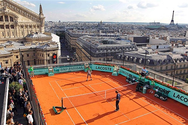 French tennis players Jo-Wilfried Tsonga (L) and Richard Gasquet (R) play on a roof-top clay court on a Paris department store.  what a place for a tennis court!