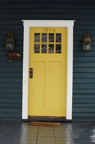 Navy blue house, thick white trim, yellow front door.