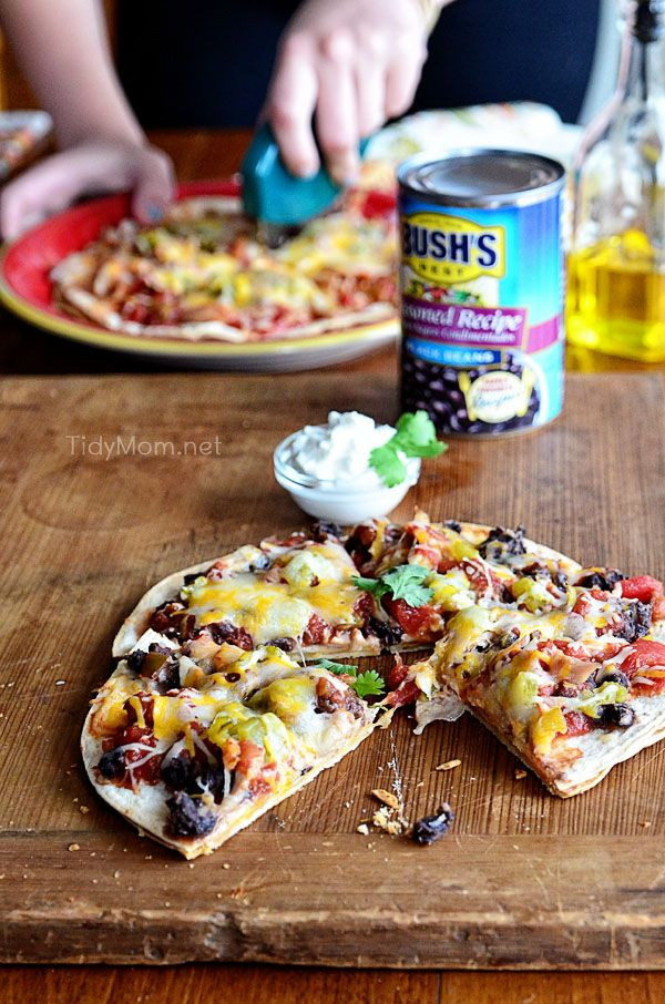 Mexican Black Bean Pizza | recipe at TidyMom.netIngredients  1 1/4 cups shredded Mexican Blend cheese 1/4 cup shredded Monterey Jack cheese 2 tablespoons olive oil 8 (6-inch) flour tortillas 1 small onion, chopped 1 (15 ounce) can BUSH'S® Black Beans, drained 1/2 cup salsa, mild or spicy 2 ounces canned chopped green chiles 2 ounces pulled chicken