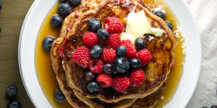 The absolute best sourdough pancakes made with whole wheat flour, kefir, and raspberries, topped with more fresh berries, butter, and real maple syrup.