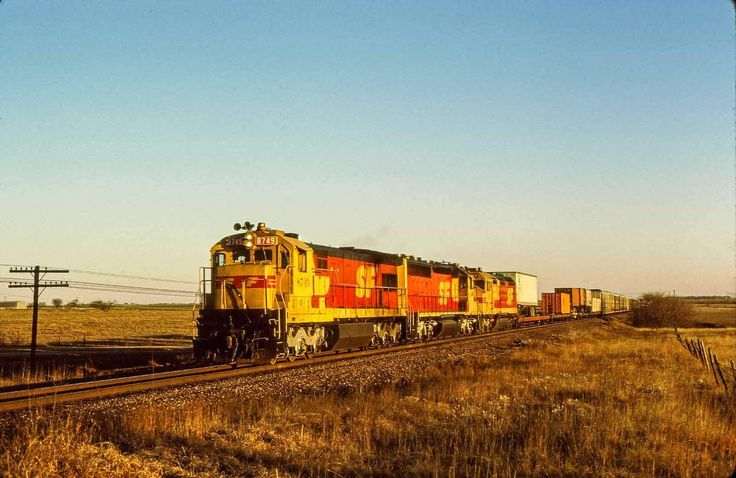 https://flic.kr/p/22ivnvp | Reds at Sunrise | Just moments after sunrise on a December 1988 morning Santa Fe U36C 8749 leads a trio of merger reds on train 165 near Justin, TX. Only a couple U36C's were painted red so I wasn't all that disappointed that the red cowl wasn't leading. Getting 3 reds by this late date was a pretty good catch as well. Santa Fe worked pretty hard to repaint the reminders of the failed merger back into blue.