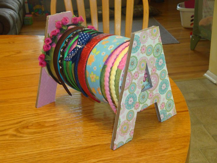 Headboard holder made with oatmeal container and letters from Hobby Lobby covered in scrapbook paper and Mod Podge. Be sure to glue one letter to the lid so you can store extras inside the oatmeal tub.