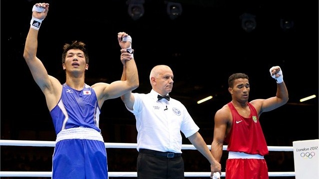 Referee Mariusz Gorny (C) announces winner Ryota Murata (L) of Japan against Esquiva Falcao Florentino (R) of Brazil during the Men's Middle (75kg) Boxing final bout