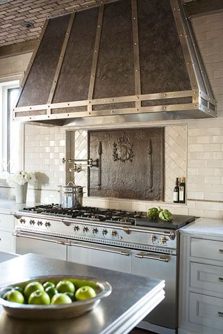 Custom zinc and stainless steel hood, Perrin & Rowe pot filler, antique fireback behind stainless LaCanche range, custom pewter countertop.