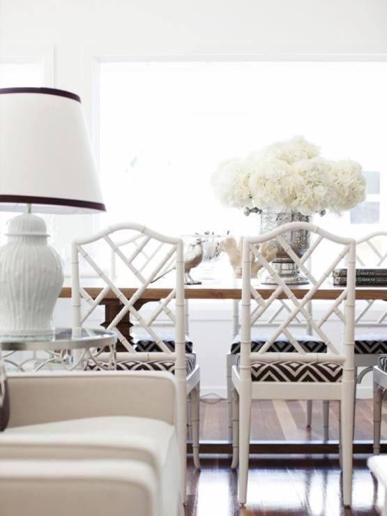 Gorgeous dining space features a rectangular wooden dining table topped with a stunning mercury glass vase filled with white hydrangeas that is surrounded by white bamboo dining chairs topped with La Fiorentina fabric seat cushions from David Hicks.